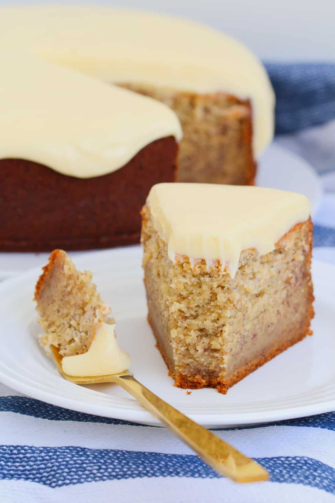 A fork full of cake with frosting next to a slice of banana cake.