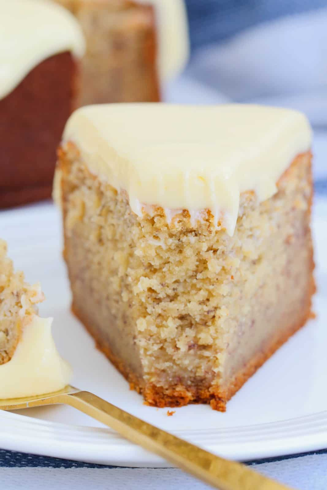 A close up of a serve of banana cake with frosting on a plate with a forkful beside.