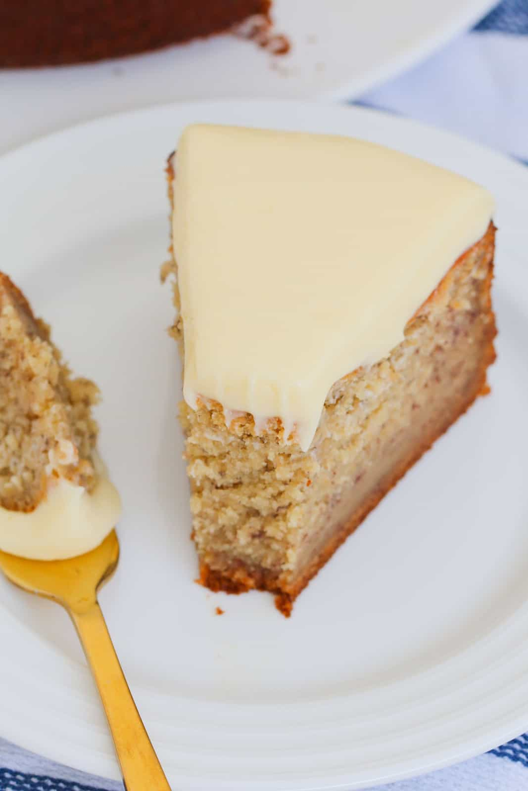 A white plate and a gold fork, with a piece of banana cake and soft cream cheese icing.