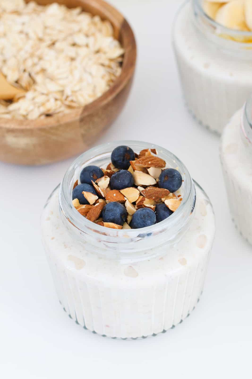 Blueberries and chopped almonds on top of a small glass jar of bircher muesli.