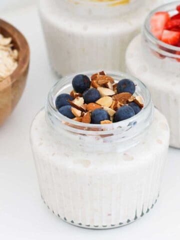 Glass jars filled with overnight oats and topped with fruits and nuts.