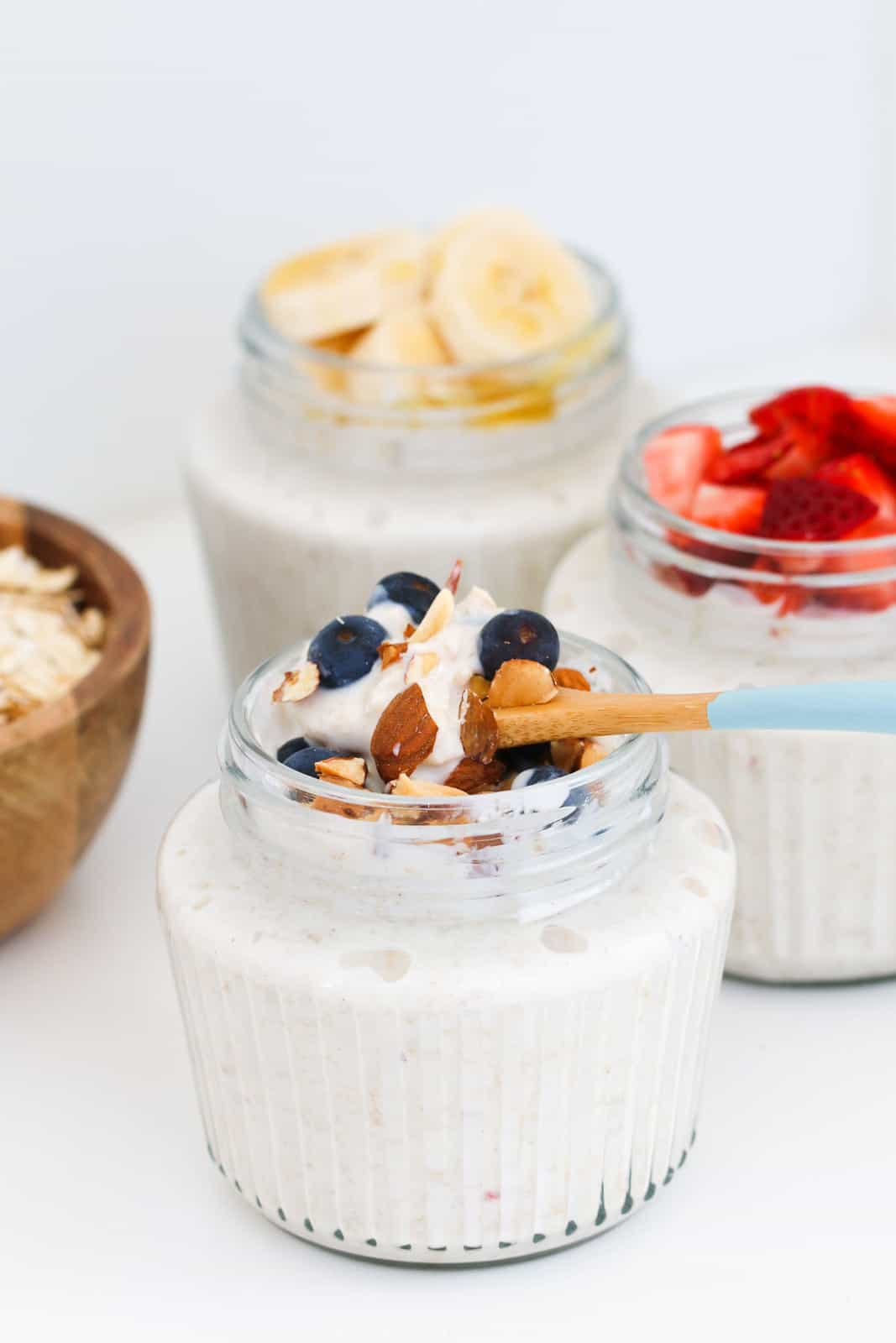 A spoon in a jar of homemade bircher muesli with nuts and blueberries on top.