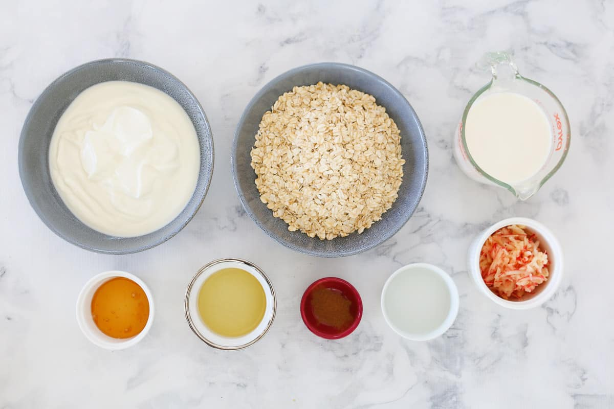 The ingredients for homemade bircher muesli in individual bowls.
