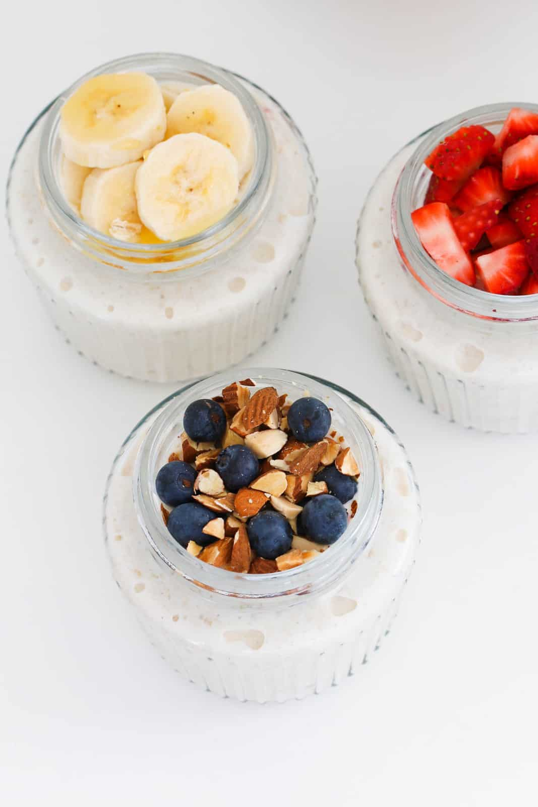 3 small glass pots filled with overnight oats and topped with fresh fruit and nuts.