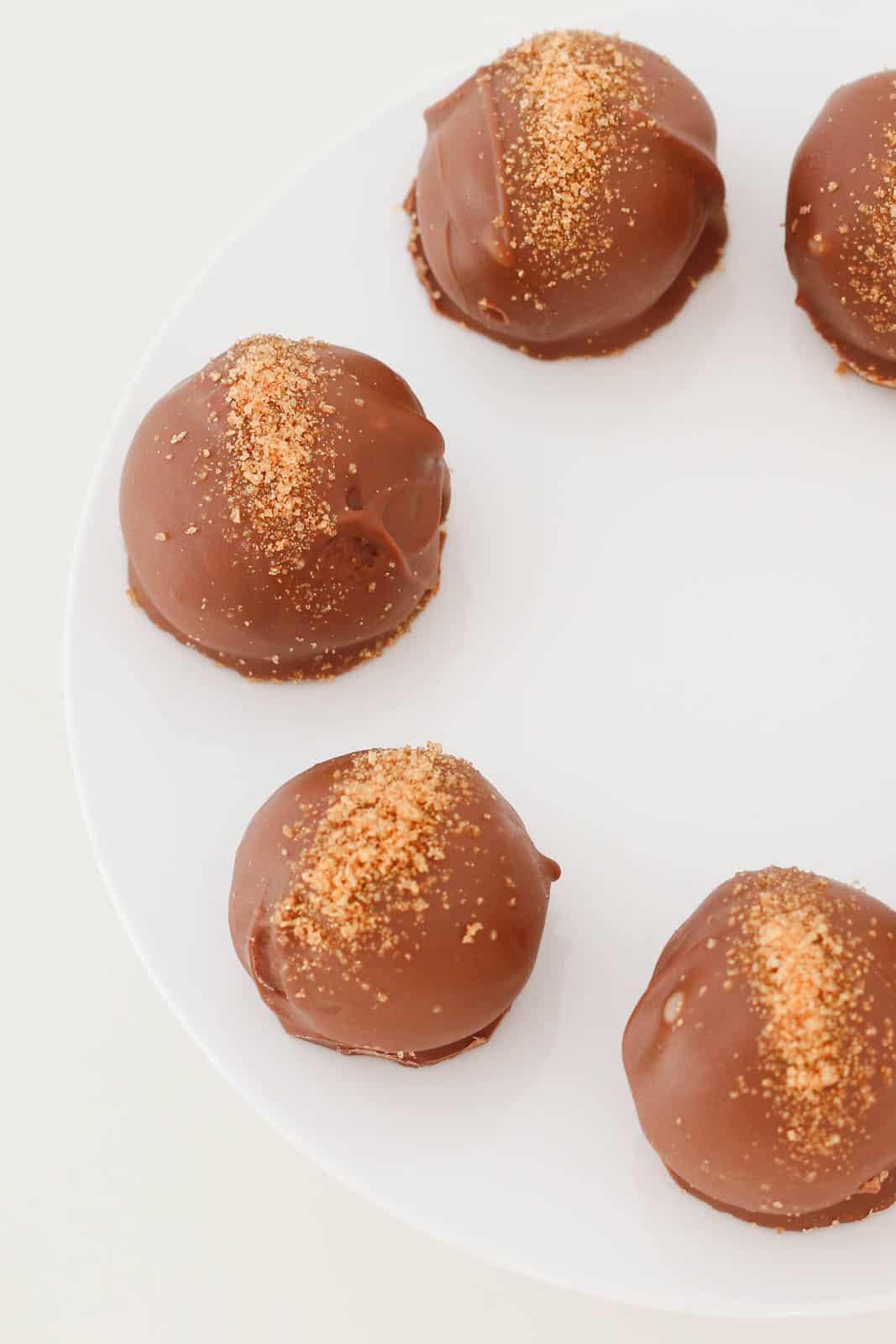 Gold sugar sprinkled over chocolate coated caramel Tim Tam cheesecake balls.