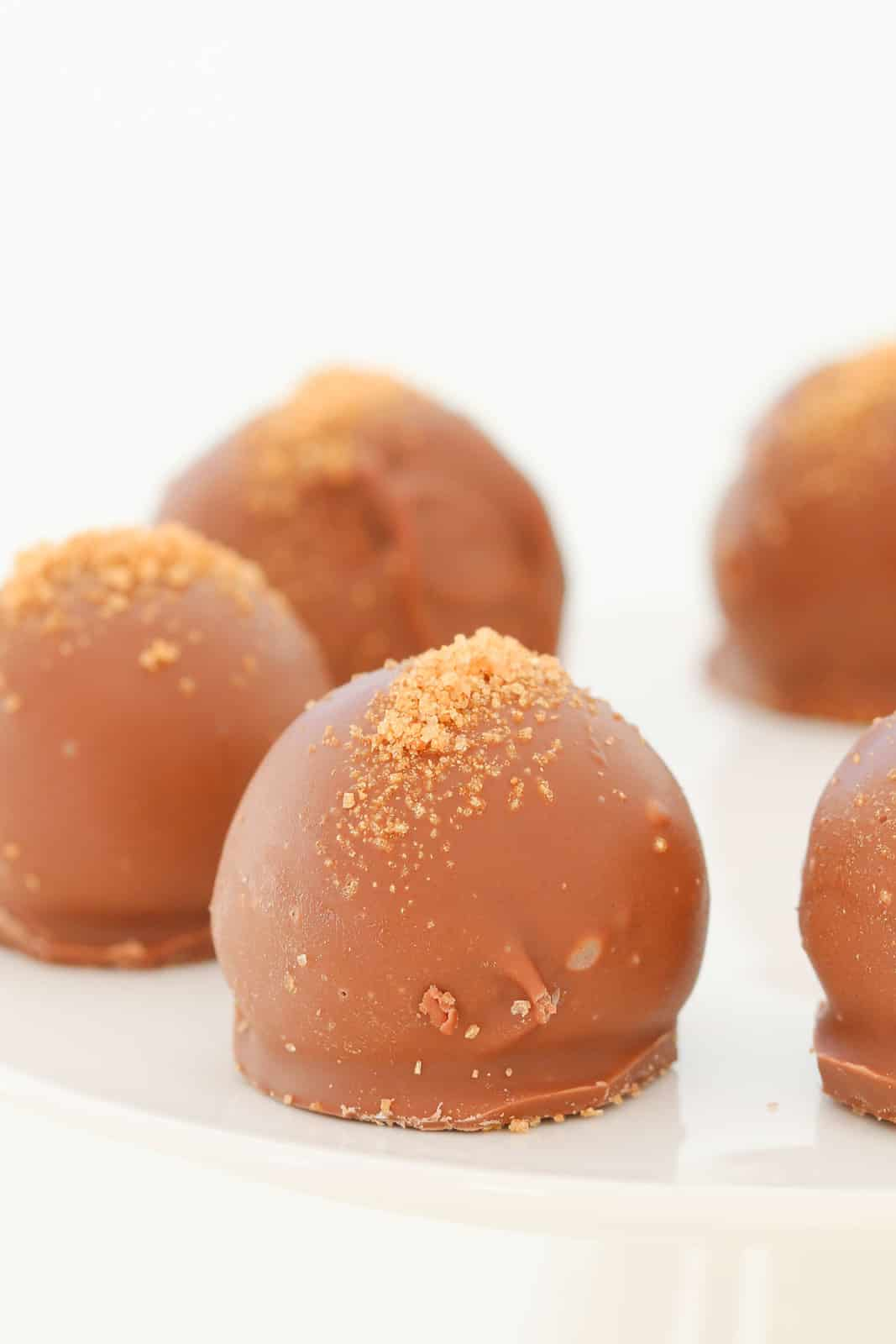 A close up of caramel Tim Tam cheesecake balls sprinkled with gold sugar.