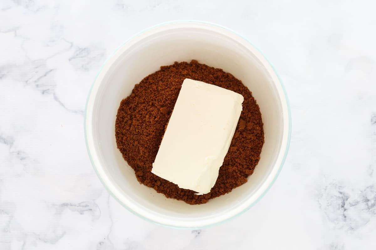 Crushed caramel Tim Tam biscuits in a bowl with a block of cream cheese.