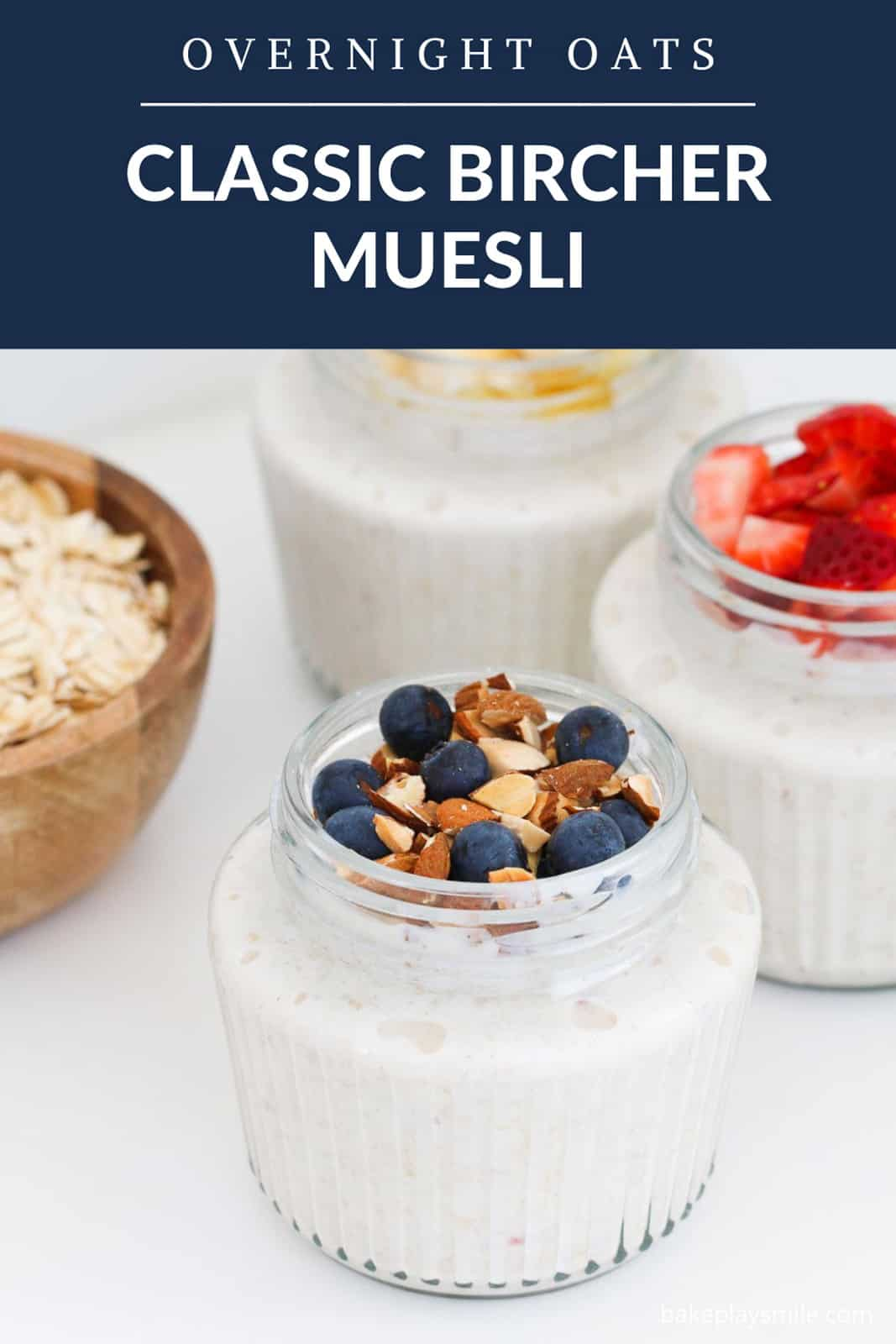 A Pinterest image of individual glass jars with fresh fruit and nuts on top, with the text overlay 'Bircher Muesli Recipe'
