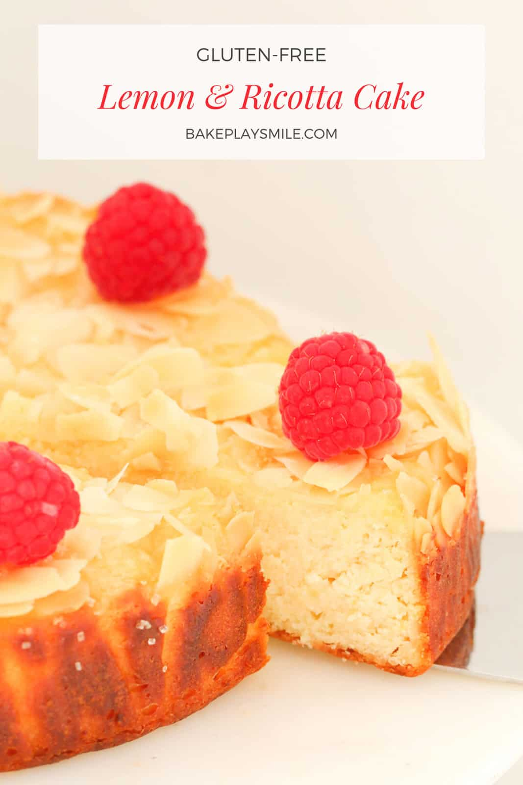 Lemon & Ricotta cake decorated with fresh raspberries and flaked almonds on a white cake stand