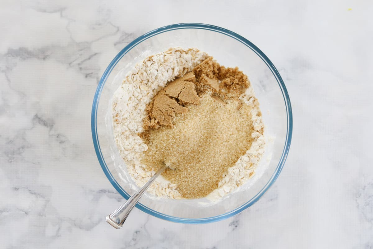 Ingredients for lemon crumble bar in a bowl mixed with a spoon