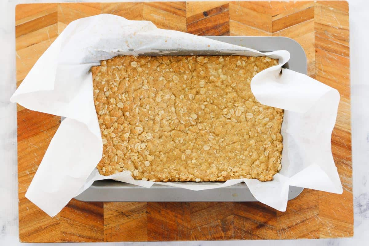 Rolled oat mixture pressed into a tin for lemon bar base.