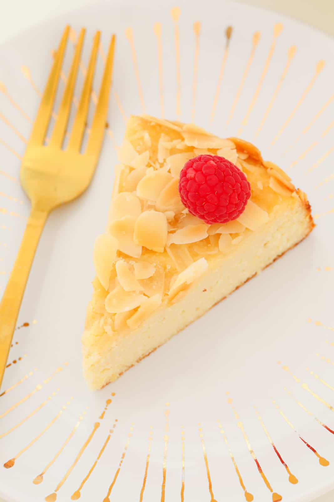Overhead shot of a serve of lemon and ricotta cake on a white plate with a gold fork