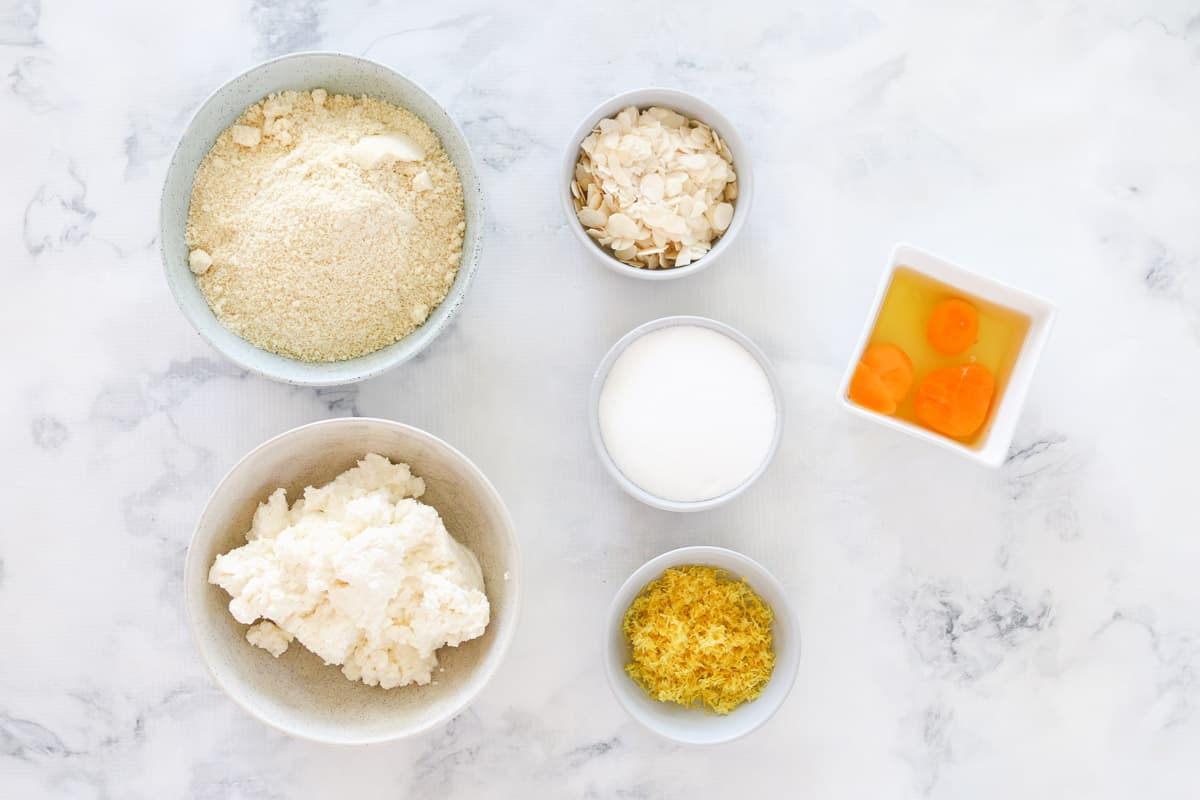 Ingredients for lemon & ricotta cake in bowls on a white counter