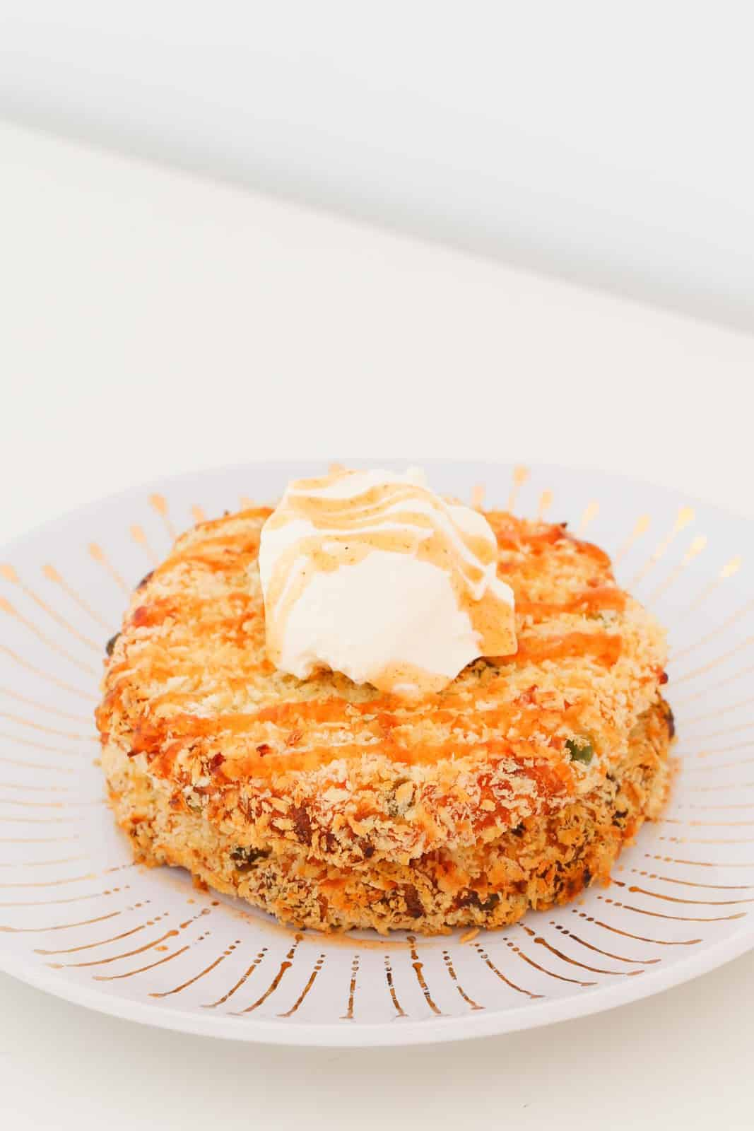 Two panko crumbed potato cakes on a white plate, drizzled with sweet chilli sauce and a dollop of sour cream.