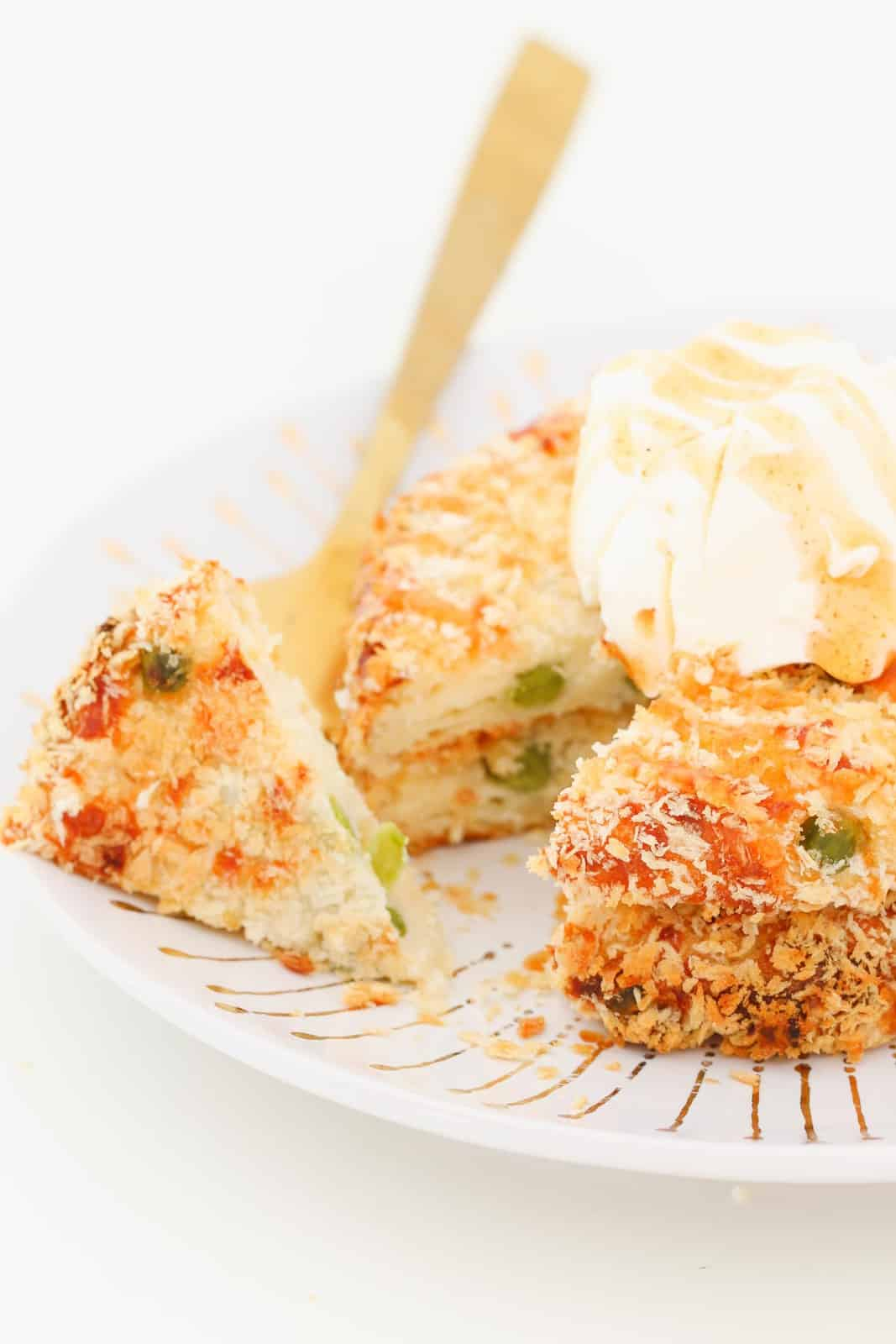 A gold fork with a piece of mashed potato cake coated in panko crumbs on it with a doloop of sour cream on the rest of the crispy potato cake.