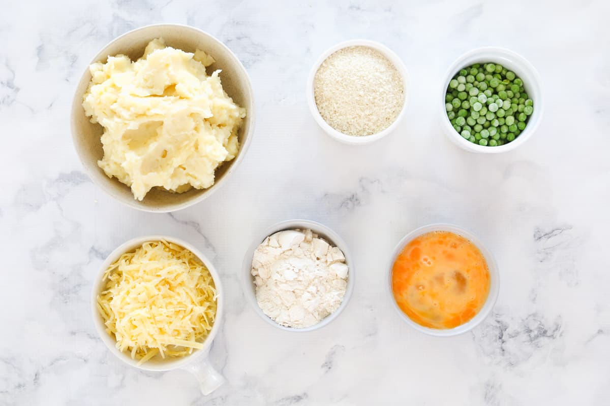 The ingredients for oven baked mashed potato cakes in separate bowls.