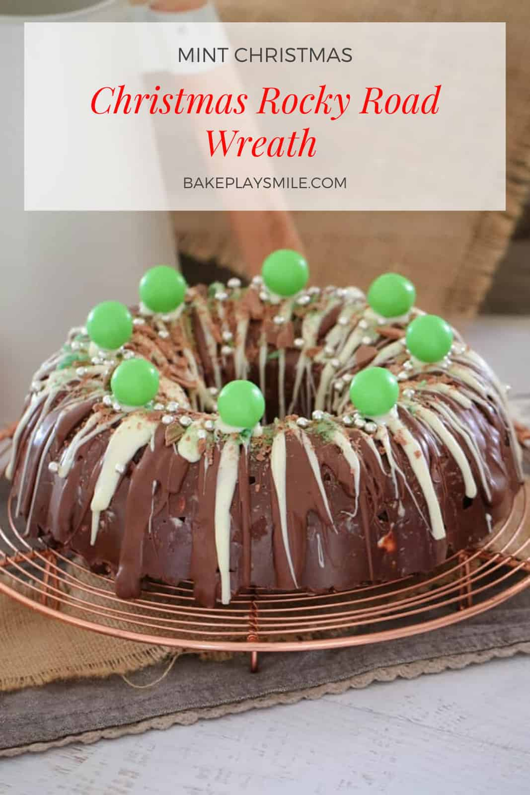 A decorated Mint Rocky Road Christmas Wreath with white and milk chocolate drizzled over, placed on a round copper wire tray