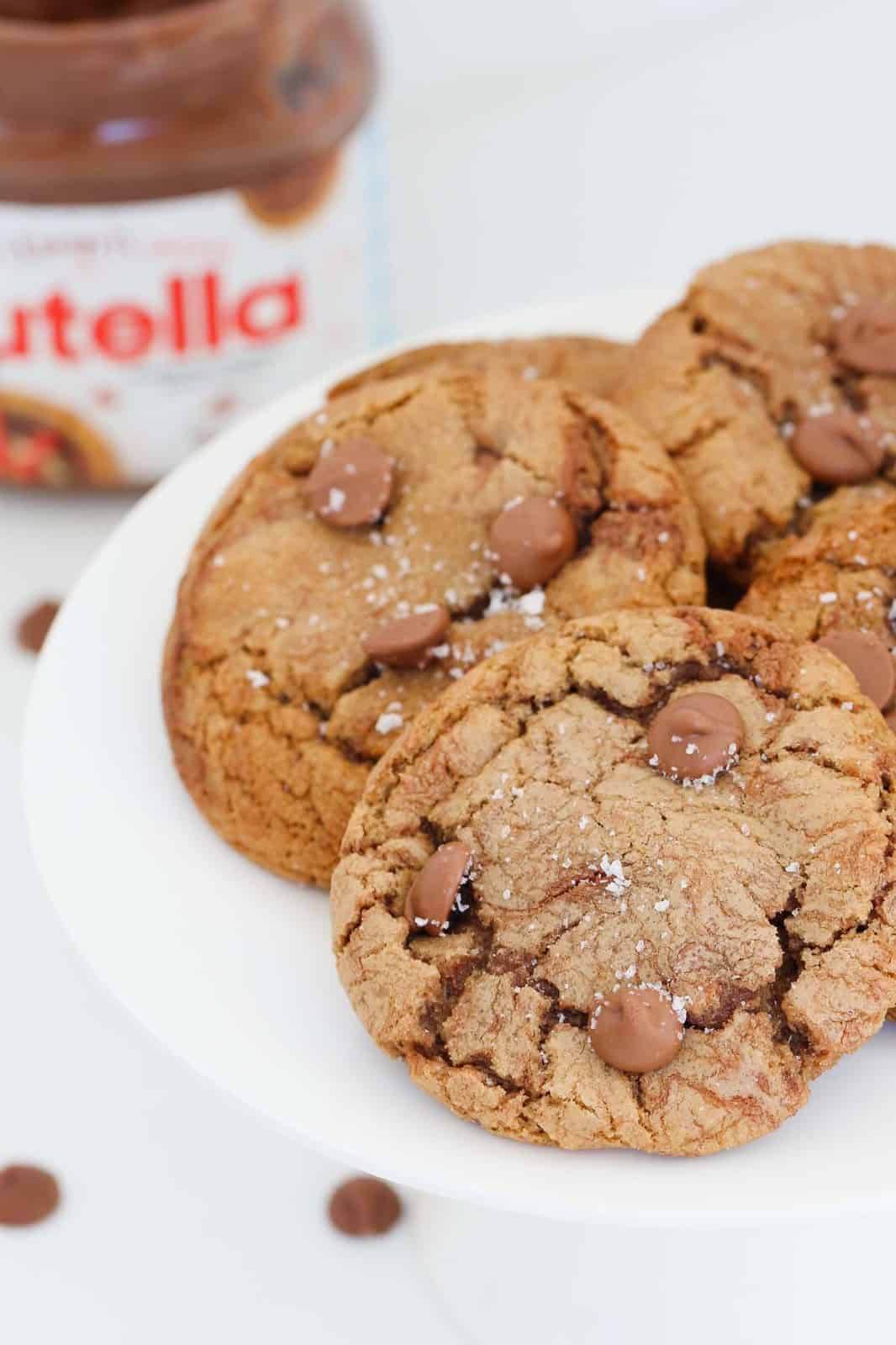 A close up of Nutella cookies with chocolate chips and sea salt on top served on a white cake stand.