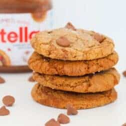 Four brown cookies in a stack with chocolate chips surrounding them and a jar of Nutella.