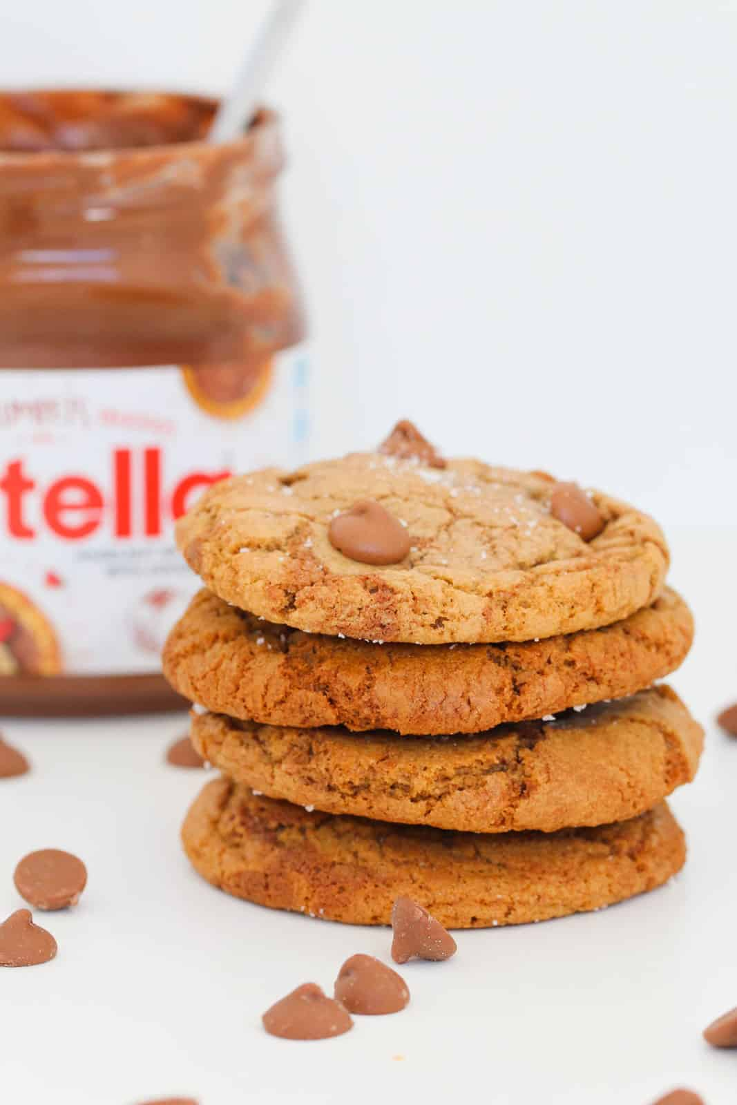 A stack of four cookies with chocolate chips and a jar of Nutella in the background.