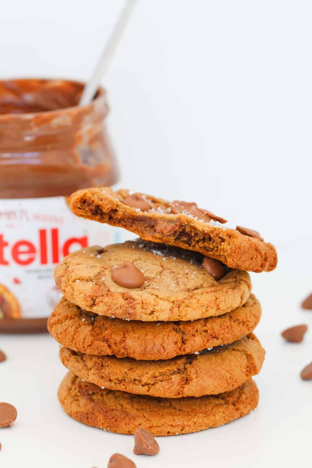 A stack of cookies with chocolate chips with one half eaten on top, and a jar of Nutella in the background.