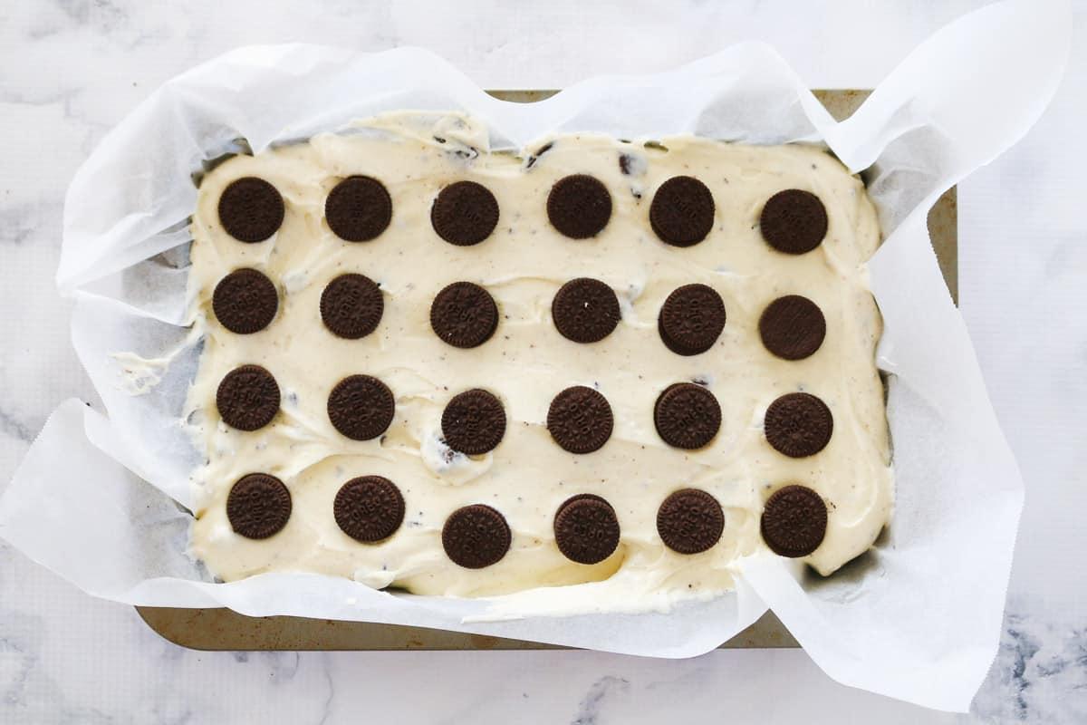Mini Oreos in rows on top of Oreo cheesecake slice
