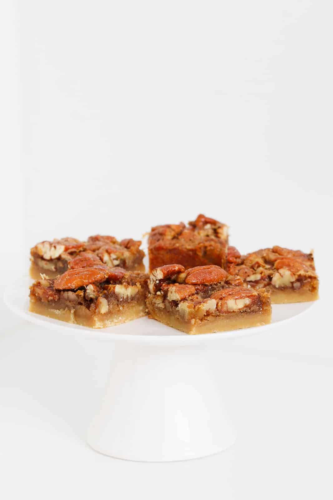 Pecan pie bars on a white cake stand