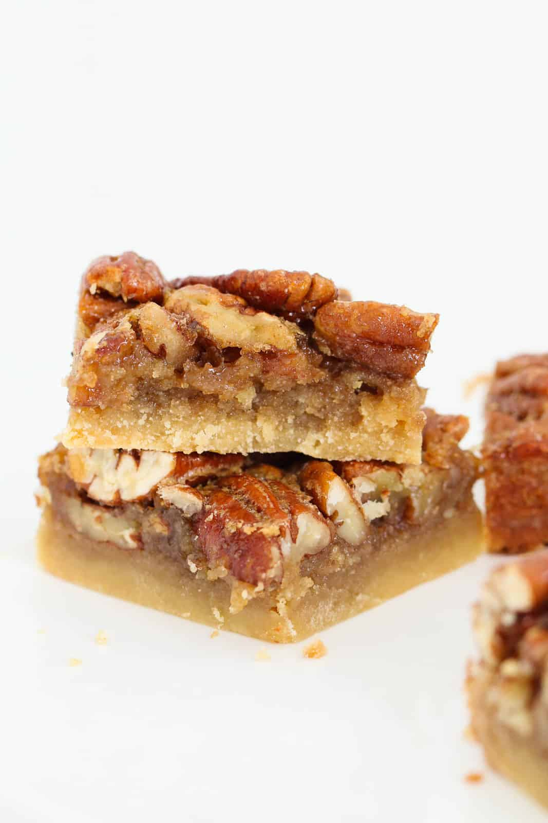 A close up of two pecan pie bars stacked on top of one another