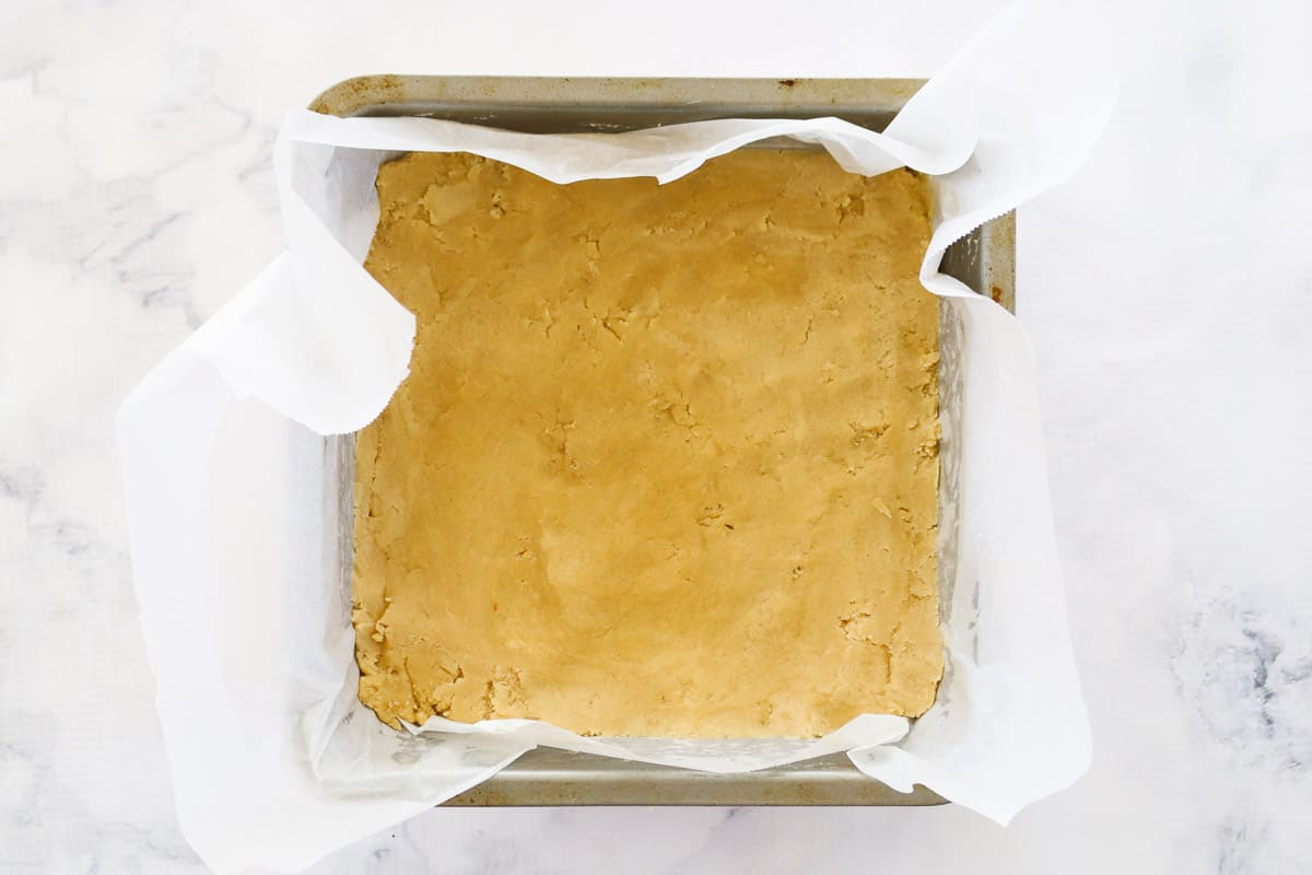 Pecan pie bars base pressed into a parchment paper-lined tin