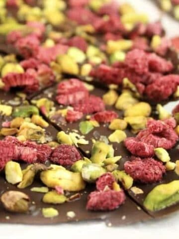 Dark chocolate bark with pistachios and dried raspberries being cut up on a board.