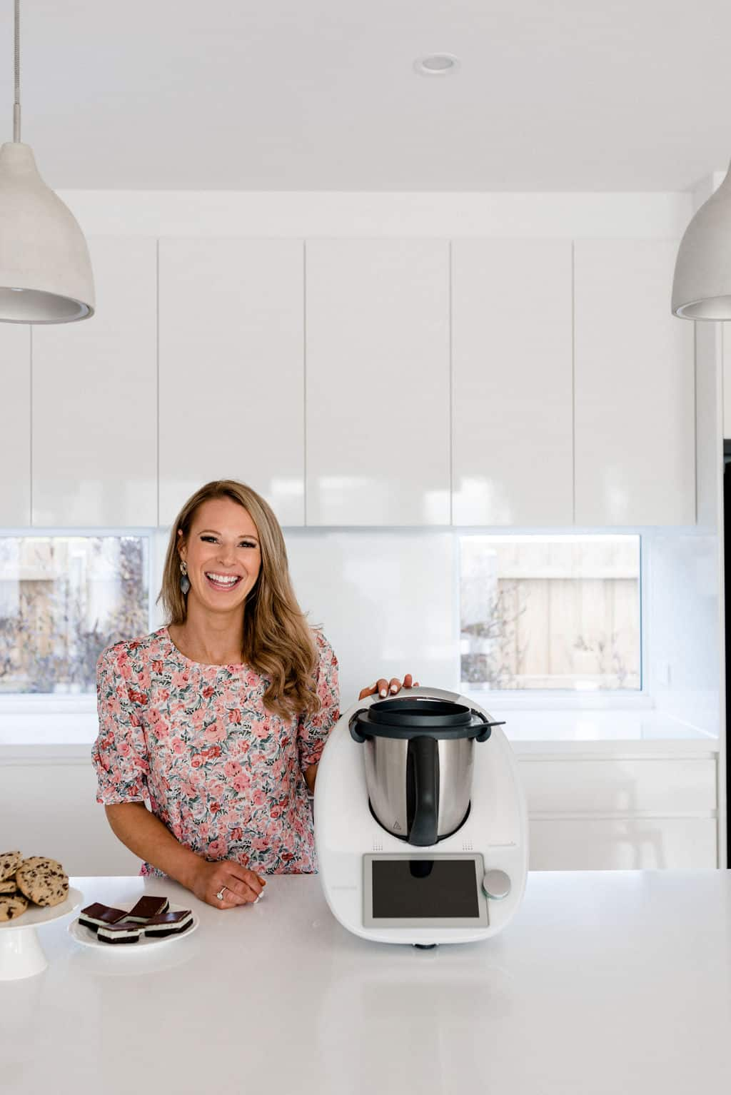 A female standing beside a Thermomix machine in a pink floral dress.