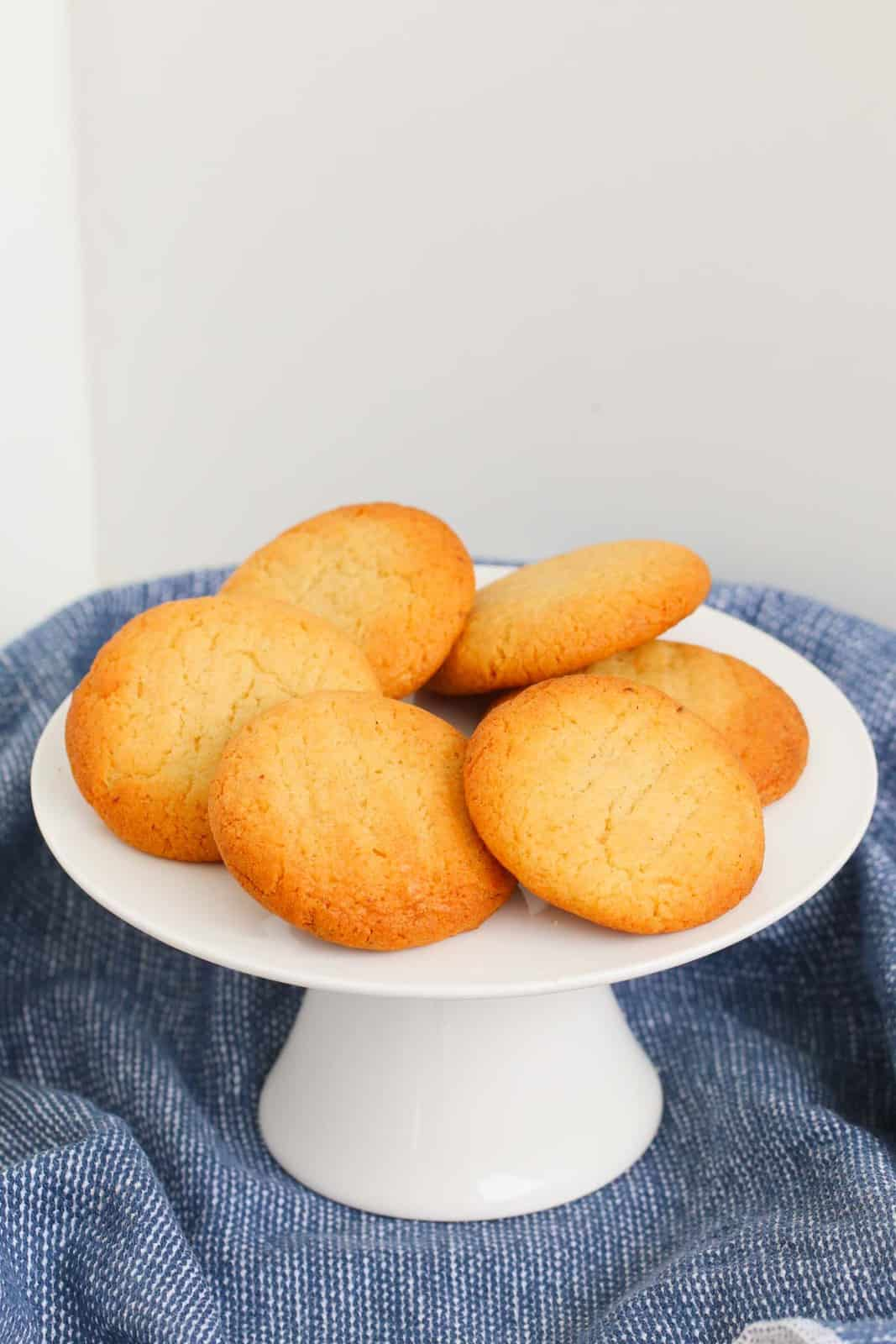 A white cake stand filled with golden honey cookies.