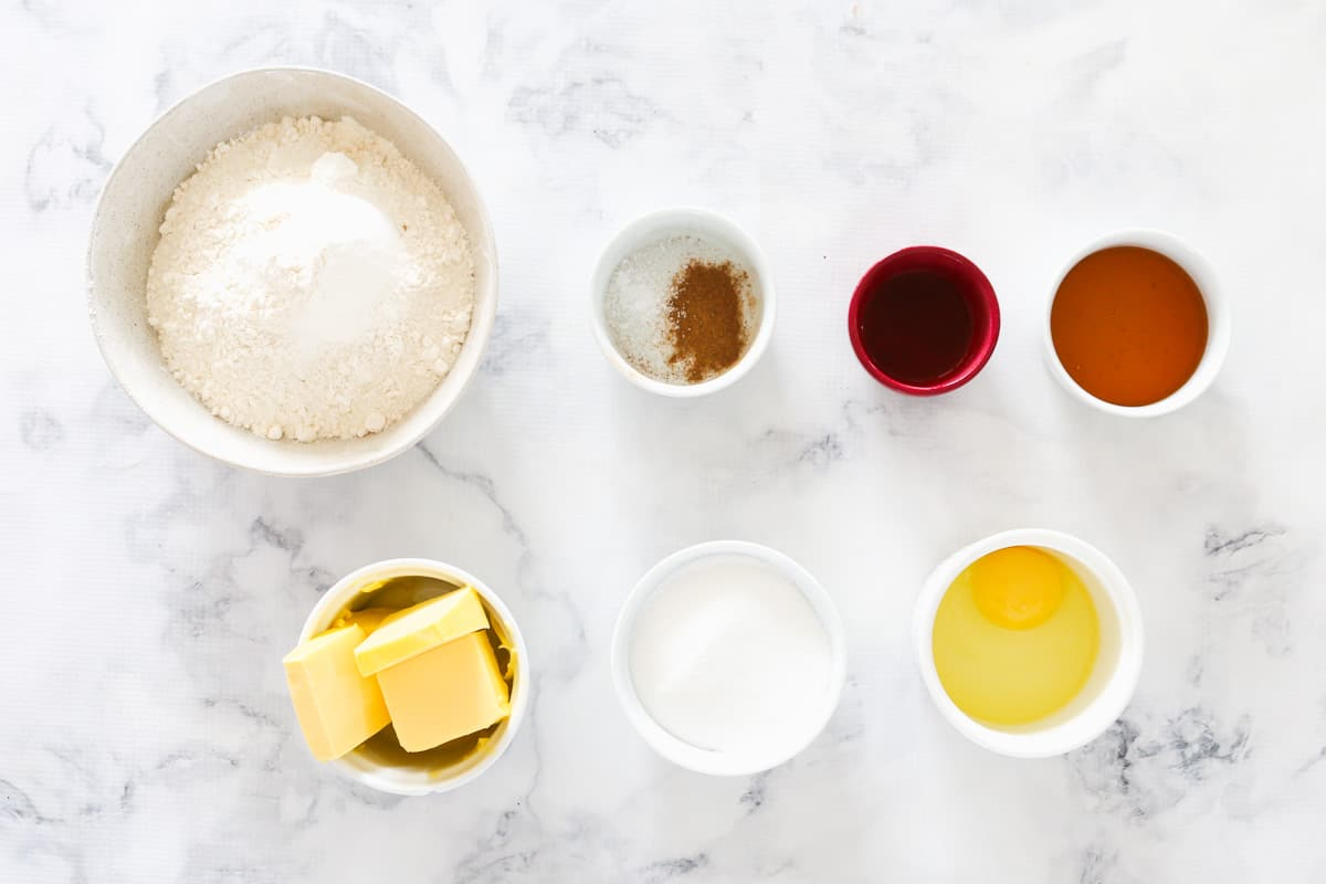 All the ingredients for honey cookies in individual bowls.