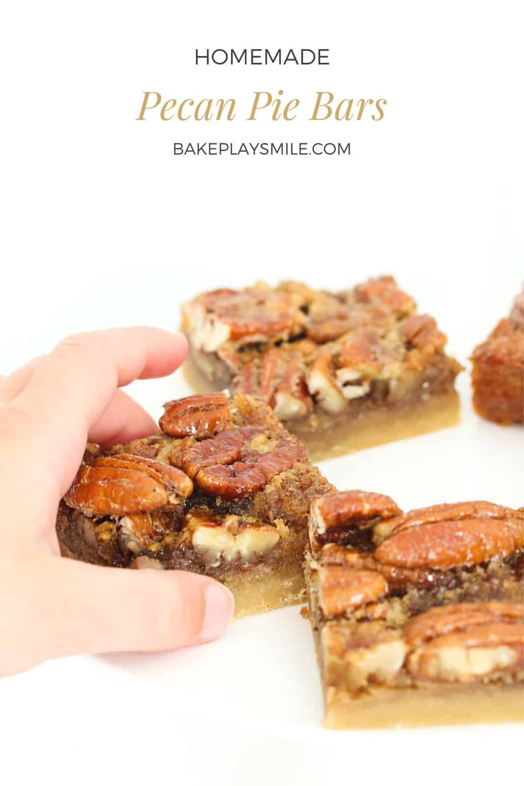 A child's hand holding a piece of caramel pecan slice.