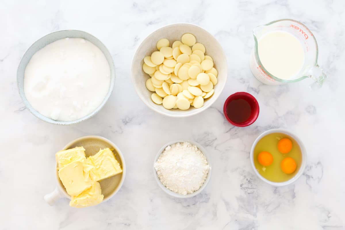 Individual bowls of ingredients for white chocolate mud cake on a white marble bench-top