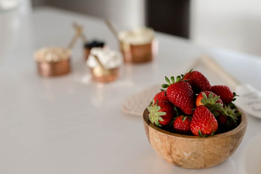 A bowl of strawberries on a white bench.