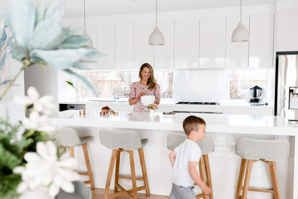 A mum and her son in a white kitchen.