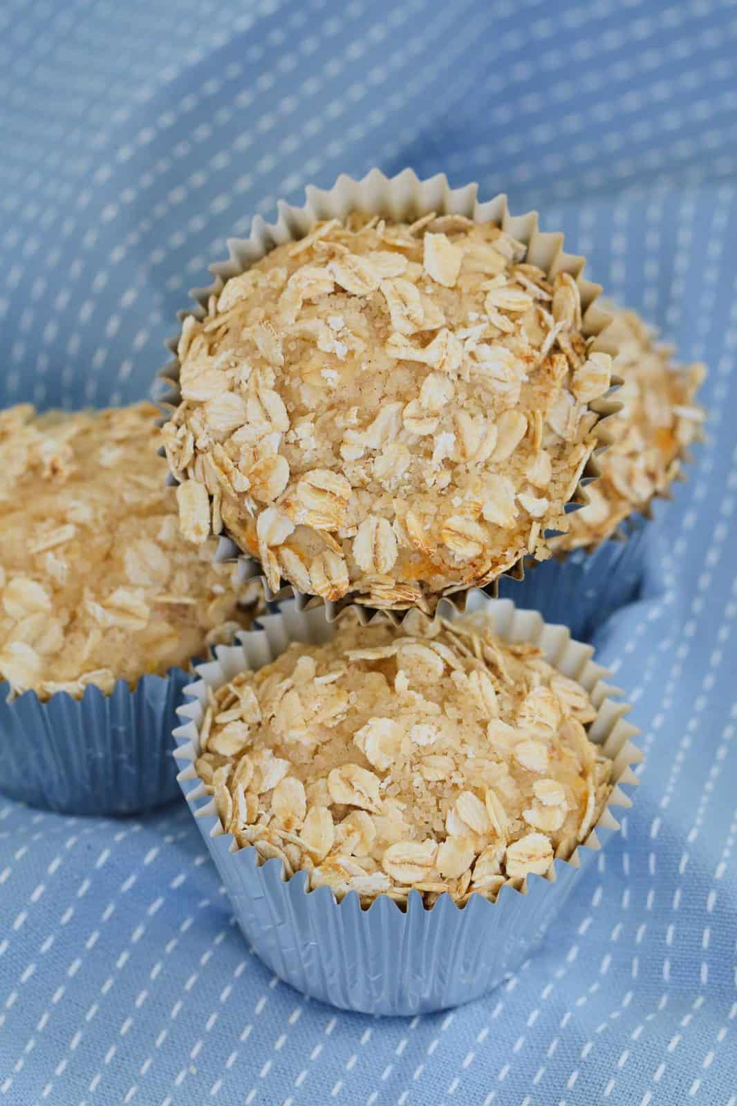 Baked apple oat muffins in blue muffin cases on blue tea towel