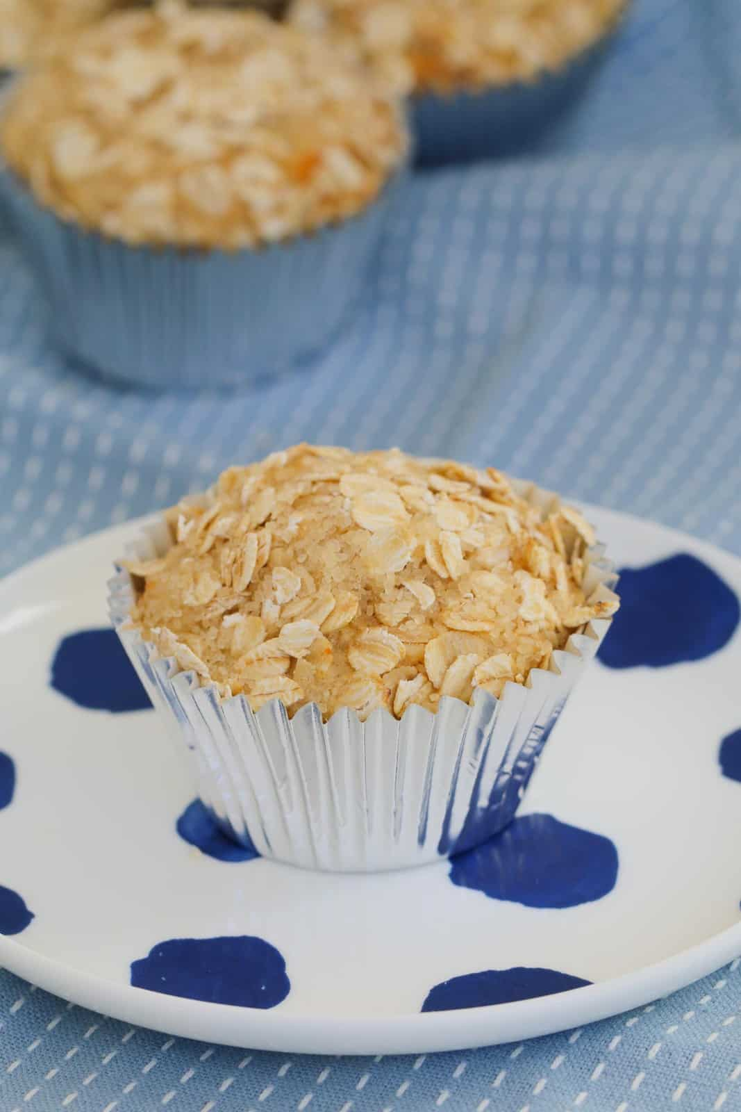 A close up shot of apple oat muffin on white plate with blue dots.