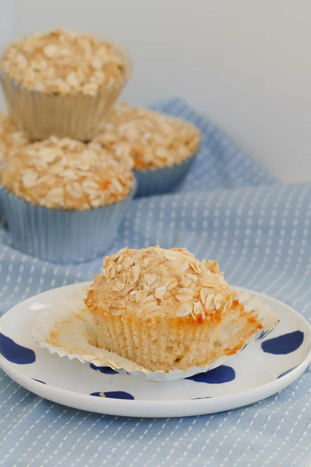 Apple oat muffins on a blue tea towel and one on a white plate in the foreground