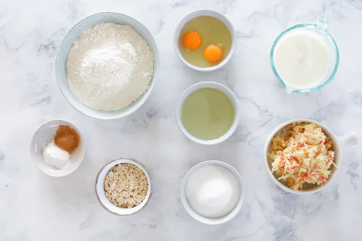 Baking ingredients in individual bowls laid out on marble bench top