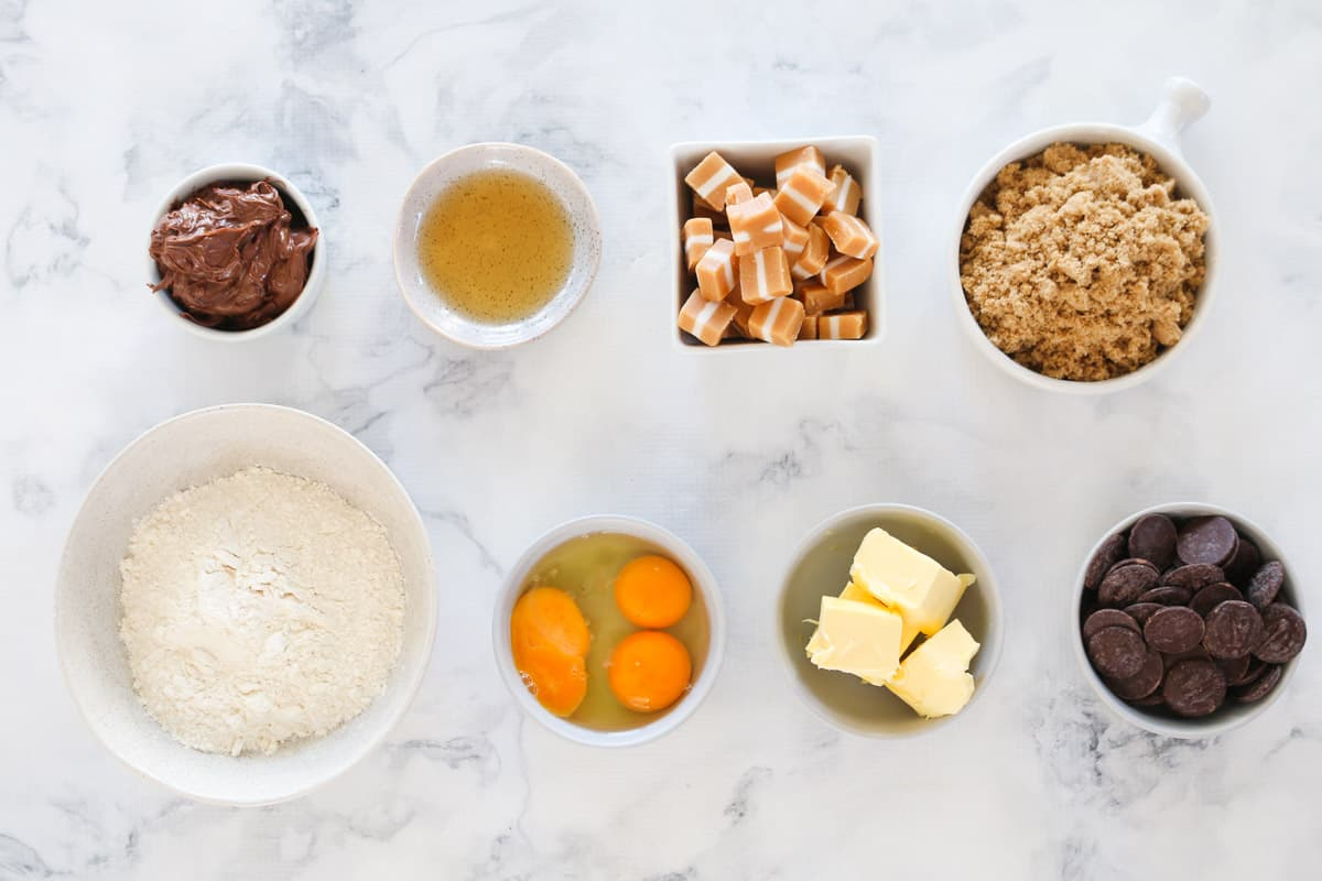 Top shot of brownie ingredients in small bowls arranged on marble countertop.