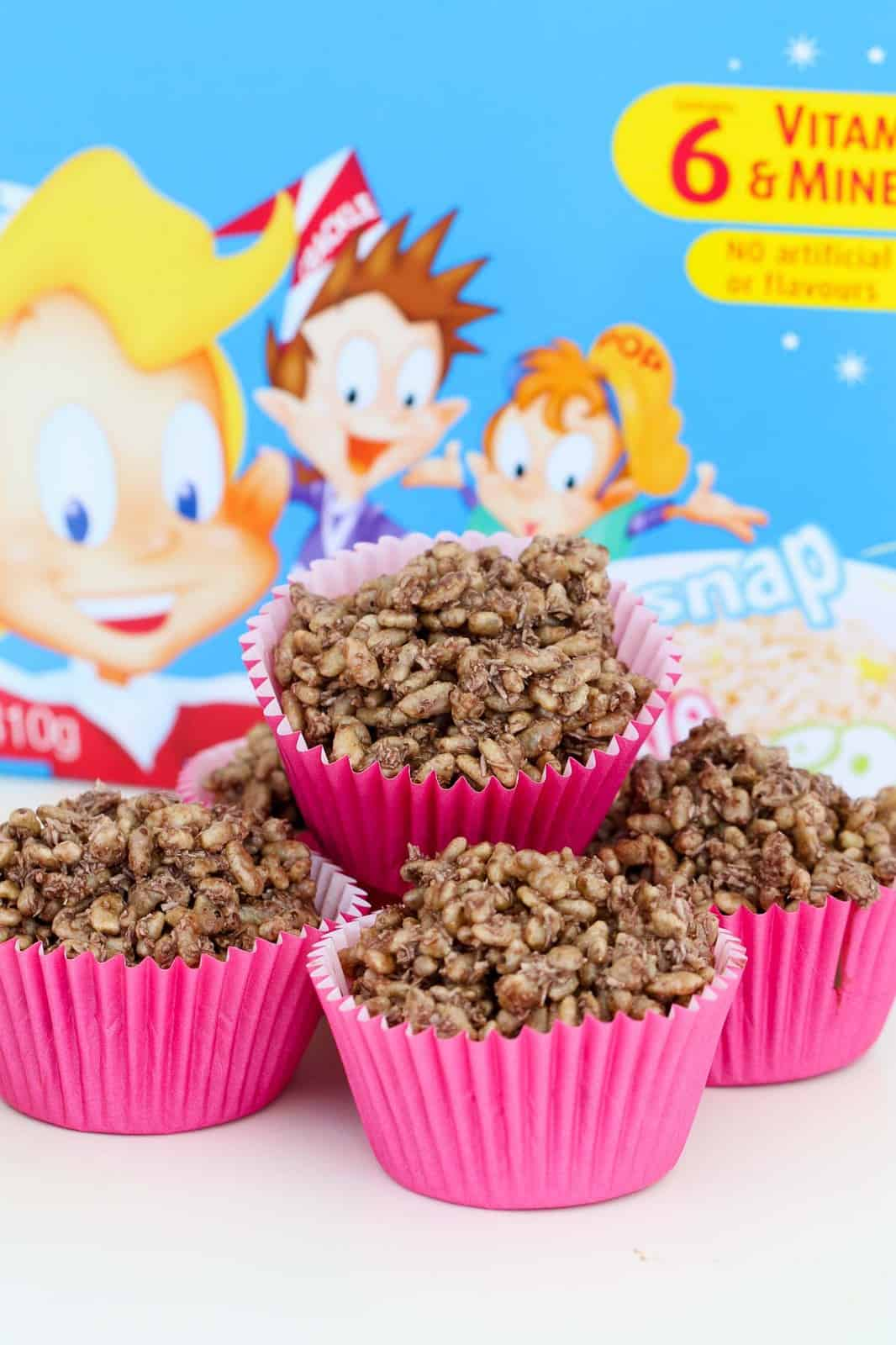 A pile of chocolate crackles in pink cases, with party decorations behind.