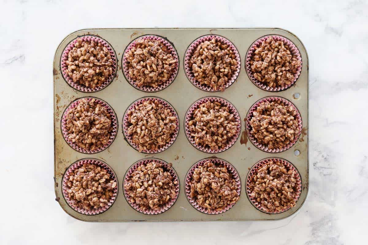 Spoonfuls of chocolate crackle mixture in cupcake liners placed in a baking tin.