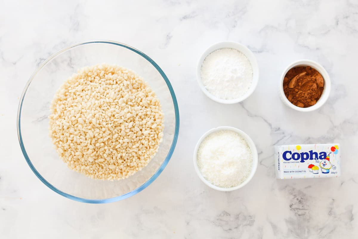 Rice bubbles, icing sugar, copha, cocoa powder, and desiccated coconut in bowls