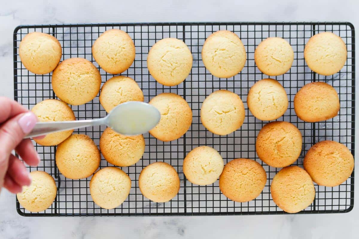 Cookies on wire rack to be  drizzled with lemon glaze
