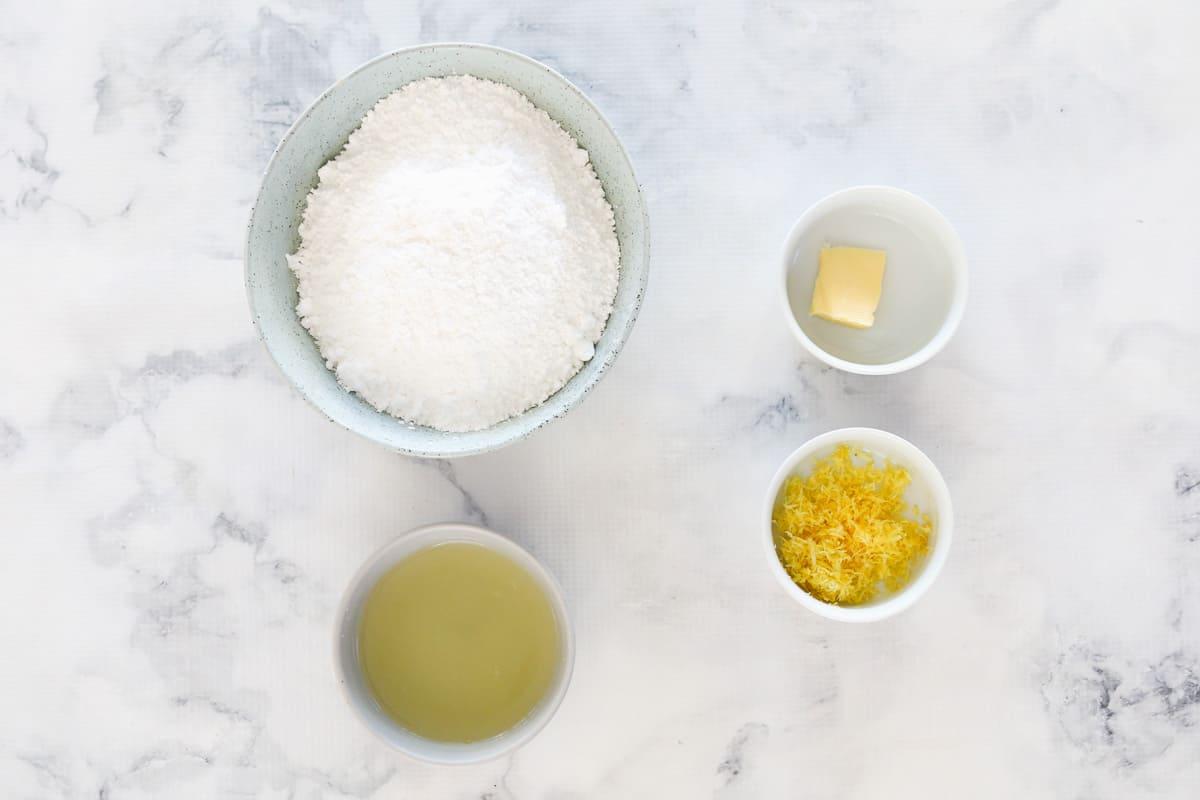 Icing sugar, butter, lemon juice and lemon zest in bowls