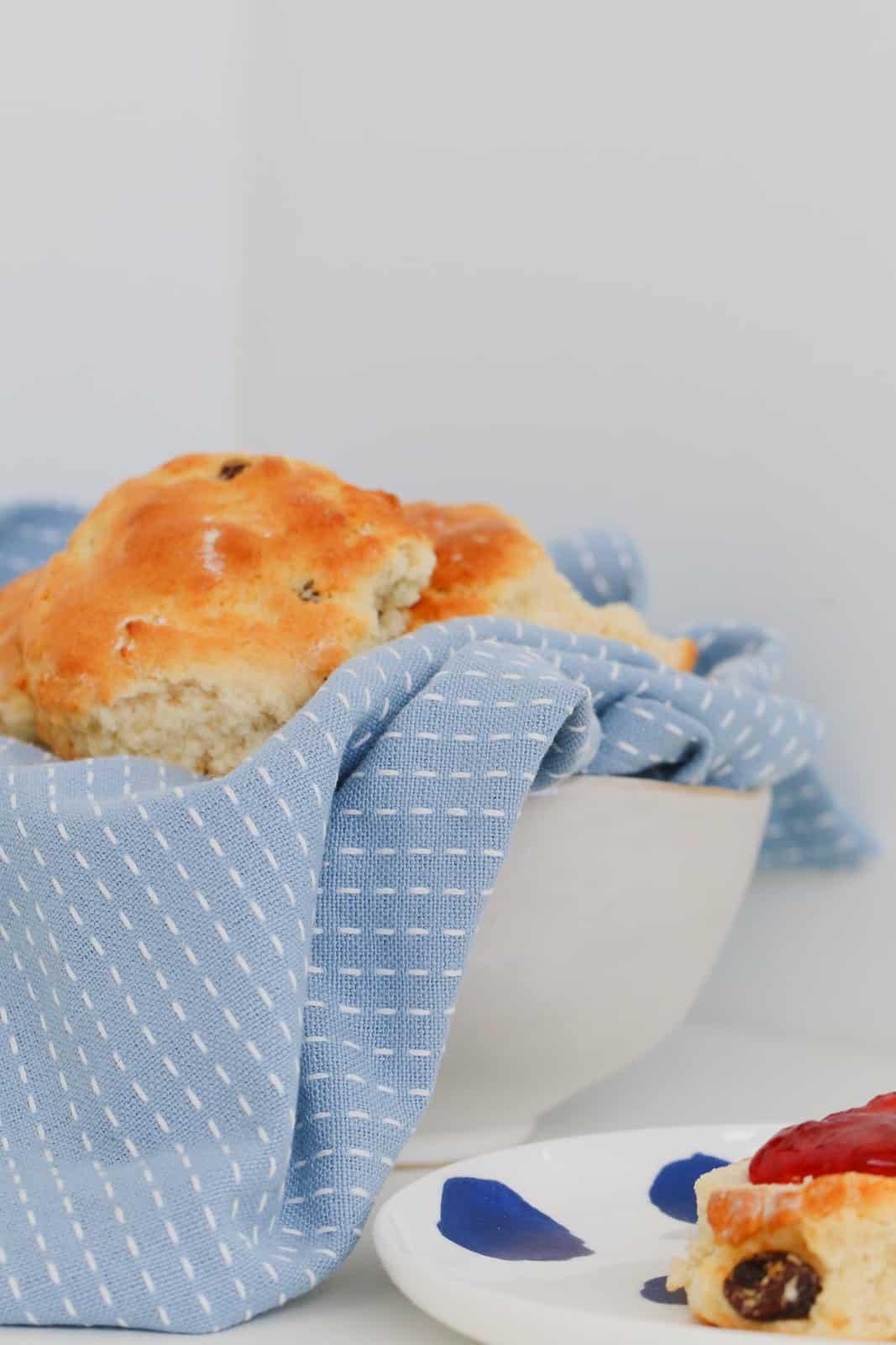 Golden fruit scones wrapped in light blue tea towel in white bowl