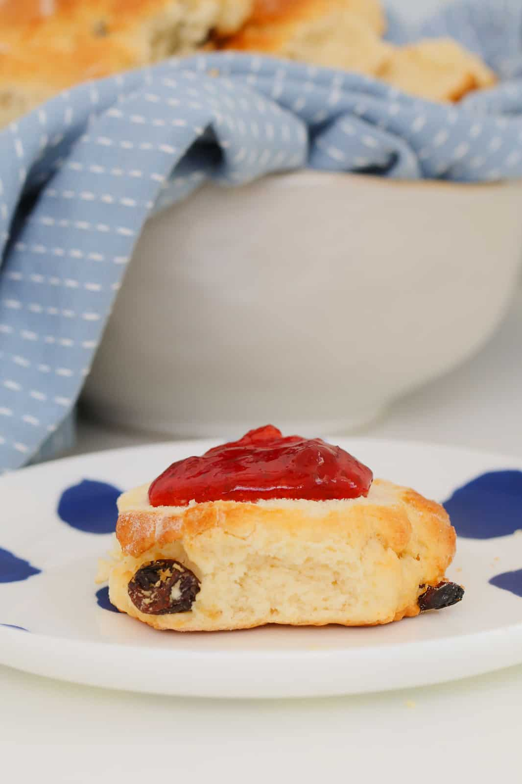 A close up shot of a fruit scone with red jam on top, sitting on white and blue plate.