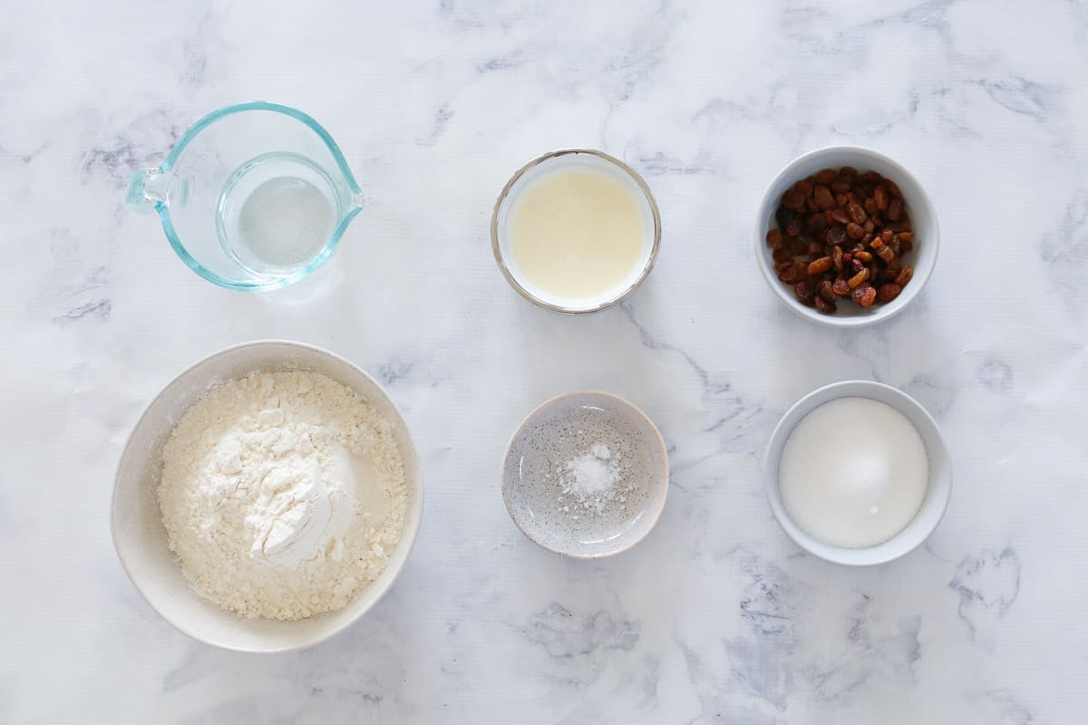 Fruit scone ingredients in individual bowls on white marble bench top.
